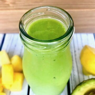 A green smoothie in a glass bottle, next to chopped pineapple and avocado.
