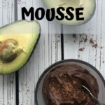 A bowl of chocolate mousse next to avocados.