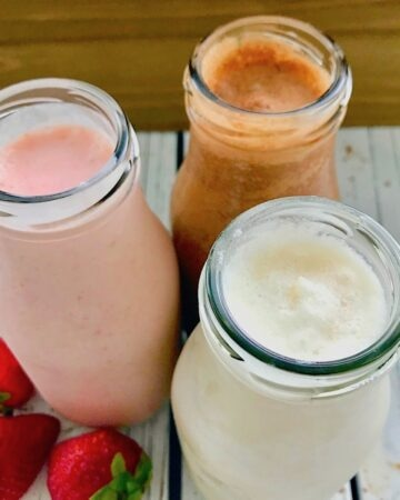 Three glass bottles with milkshakes. One chocolate, one strawberry, and one vanilla, with 3 strawberries next to them.