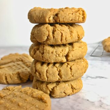 A stack of five peanut butter cookies next to two other peanut butter cookies on a table.