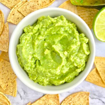 Guacamole in a small white bowl, surrounded by triangle tortilla chips.
