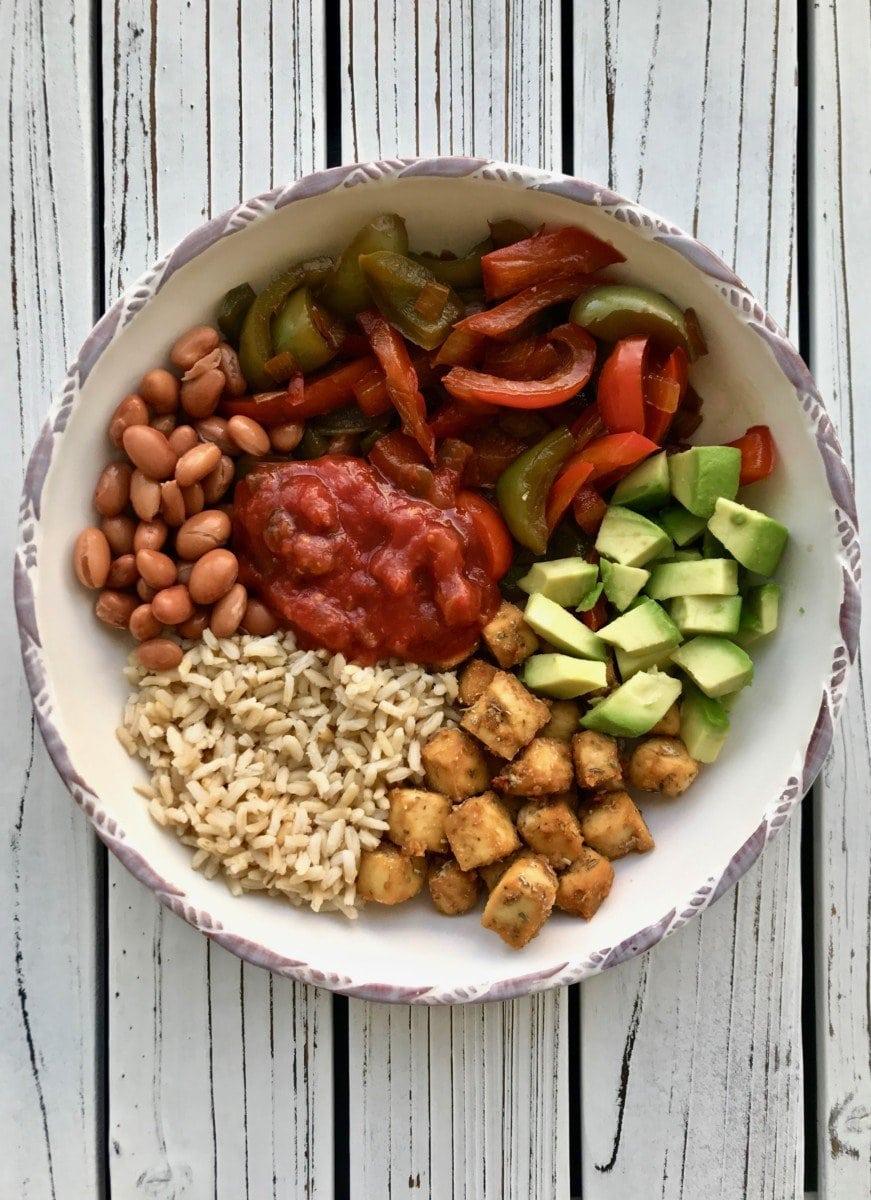 A bowl of rice, tofu, beans, and veggies.