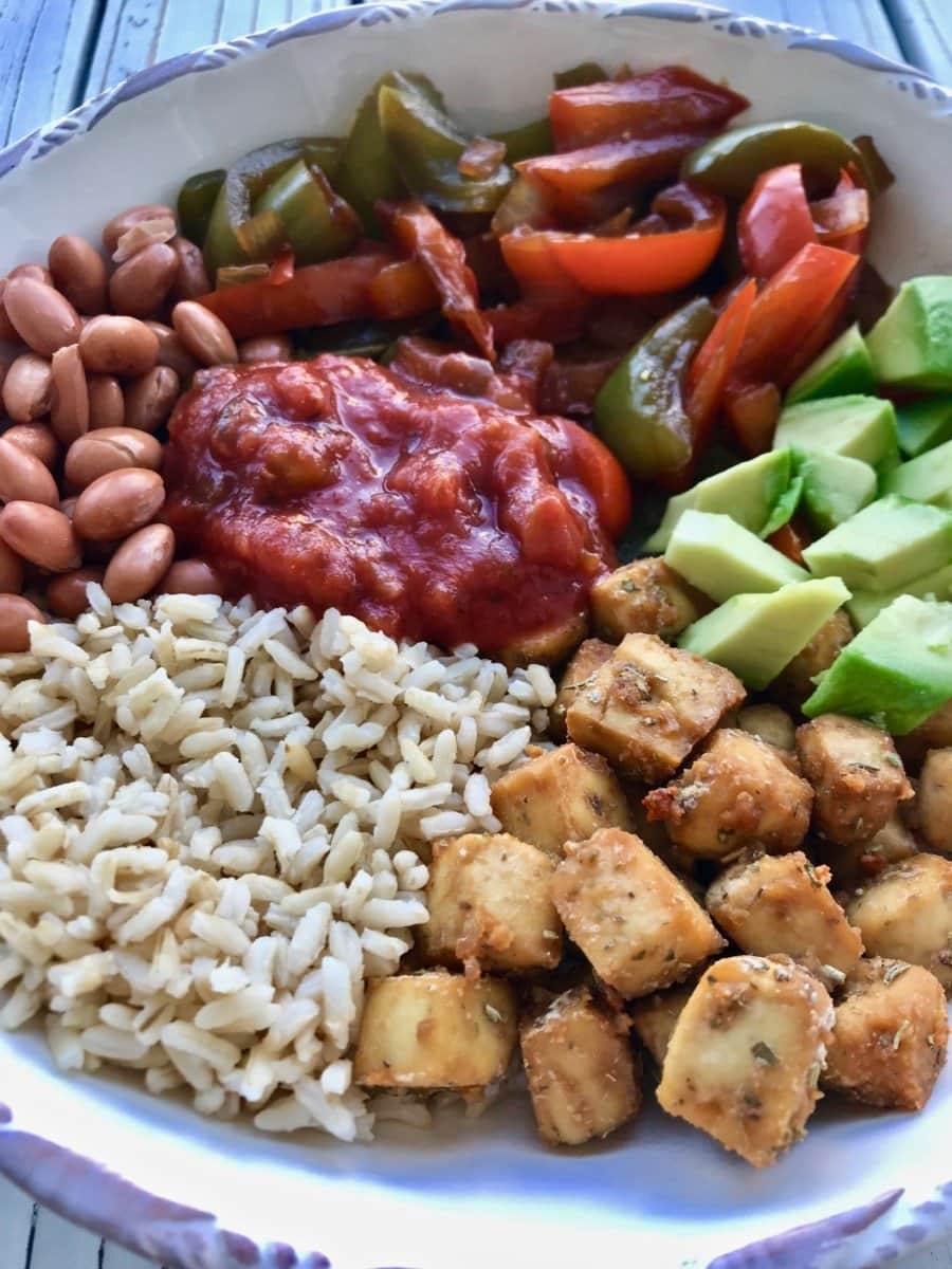 A bowl of rice, tofu cubes, avocado, beans, salsa, and cooked peppers.