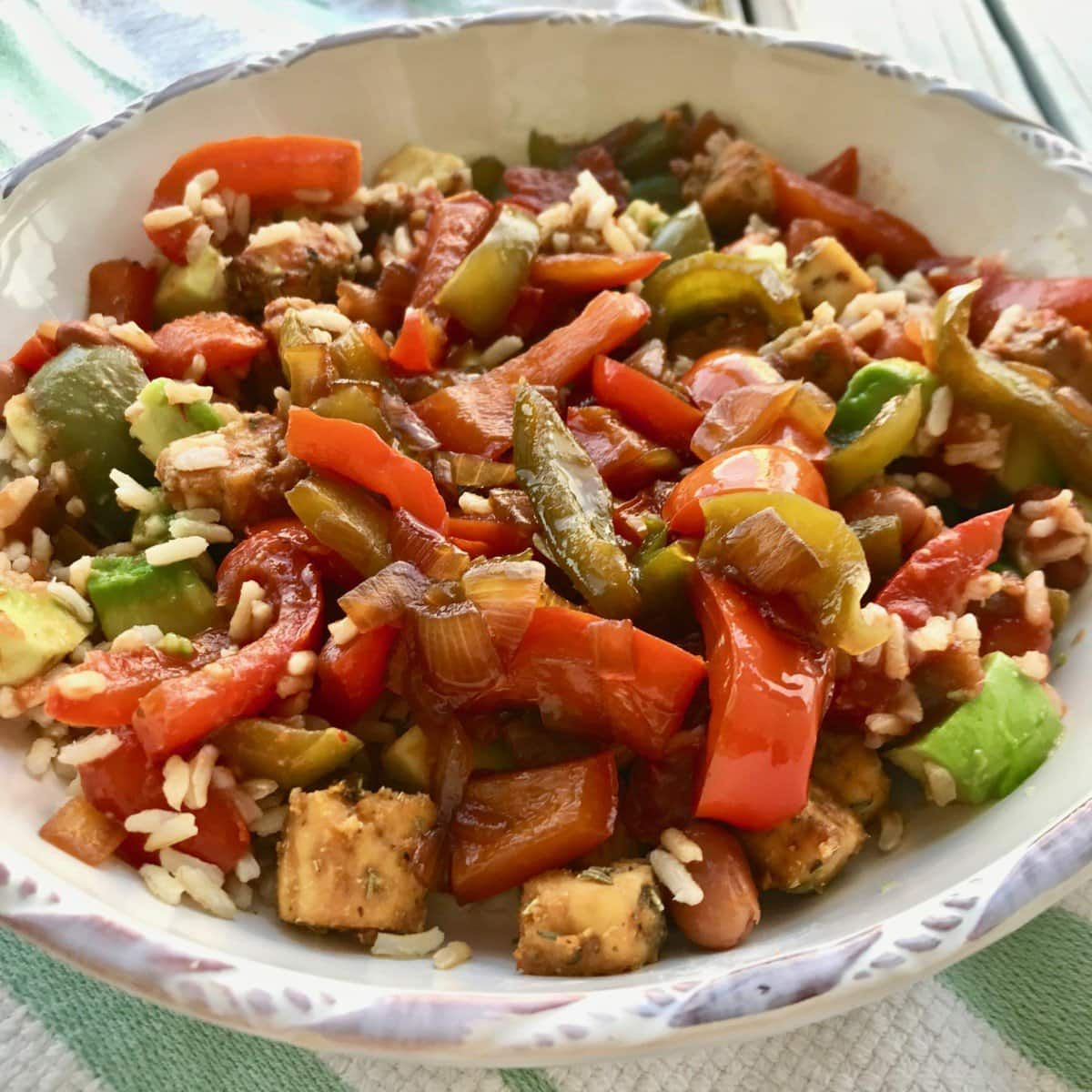 A bowl of peppers, rice, tofu, and onion.