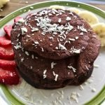 A stack of chocolate banana pancakes with strawberry and banana slices.