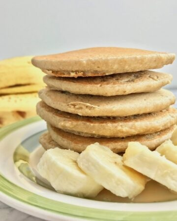Stack of pancakes on a plate with banana slices in front of the stack.