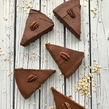Slices of chocolate sweet potato pie with pecans on top of each slice.