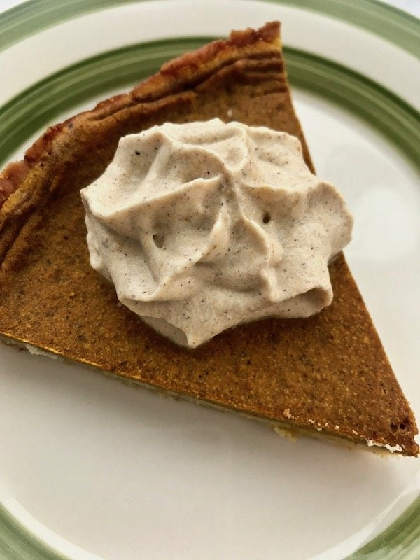 Pumpkin whipped cream on a slice of pumpkin pie.