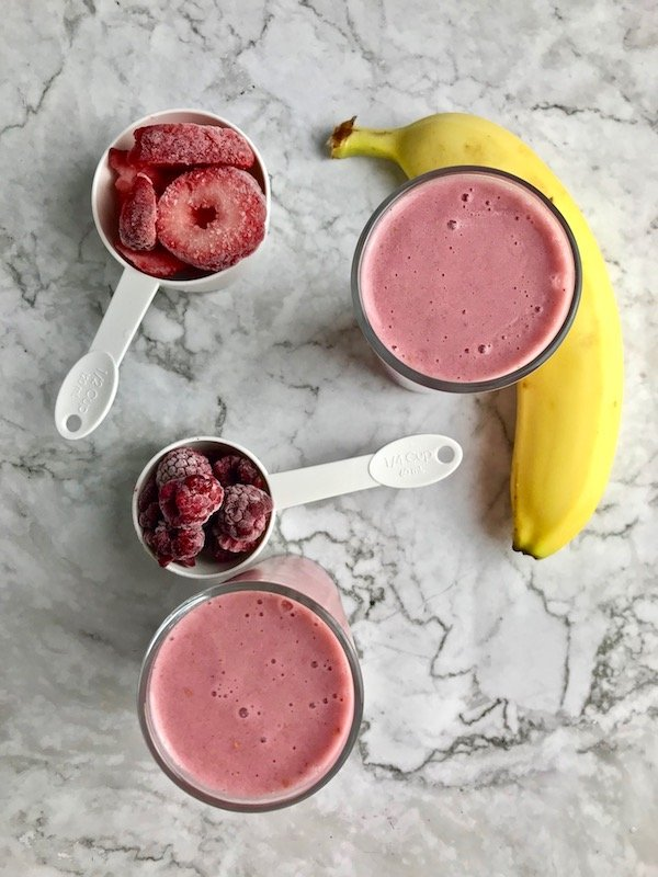 Two smoothies with banana, strawberries, and raspberries on the table.