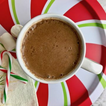 Cup of cinnamon hot chocolate on a red, white, and green striped plate, next to marshmallows and candy canes.