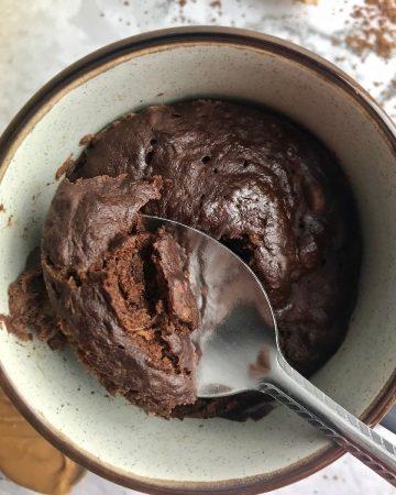 Close up overhead view of a flourless banana mug cake (chocolate) on a spoon.
