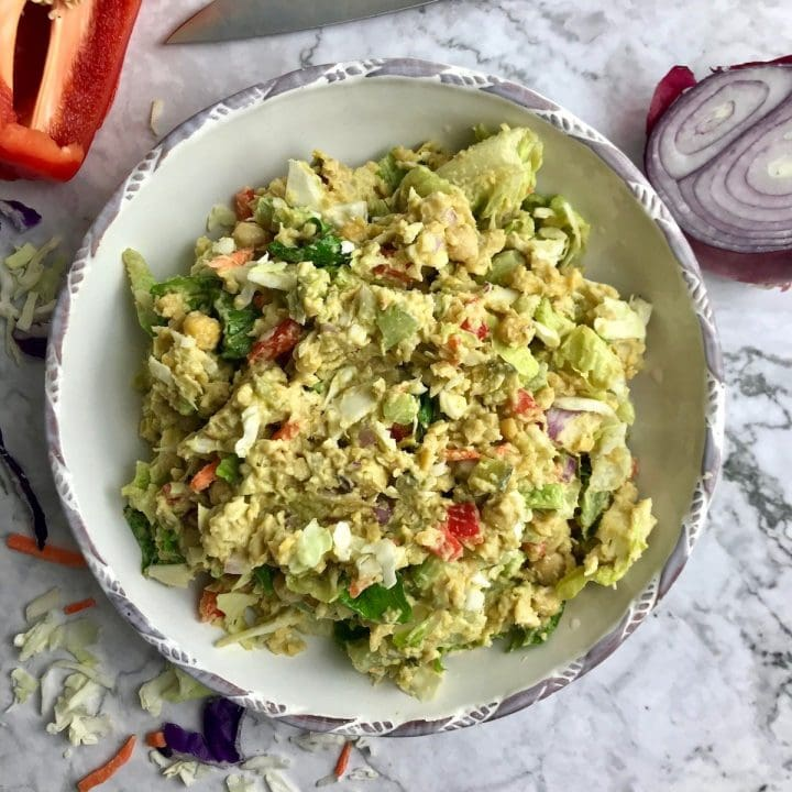 Vegan chickpea salad in a large bowl with ingredients in the background.