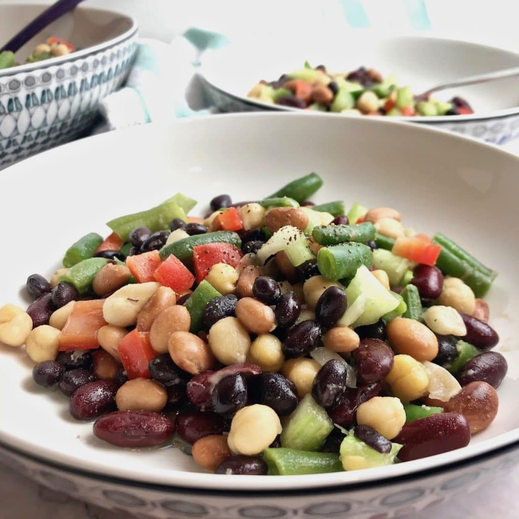 Close up of 5 bean salad in a bowl, with more in the distant background.