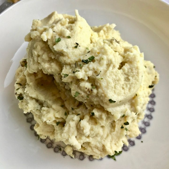 A bowl of mashed cauliflower topped with parsley.