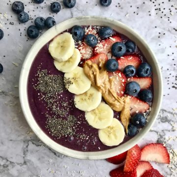 Peanut butter acai bowl topped with fruit, chia seeds, coconut flakes, and peanut butter.