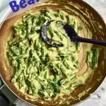 "Green beans in a pan with a cheesy nutritional yeast sauce and text, ""green beans vegan and oil-free""."