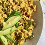 "Half a bowl of tofu scramble with avocado slices and text that says, ""Tofu Scramble Easy vegan breakfast recipe."""