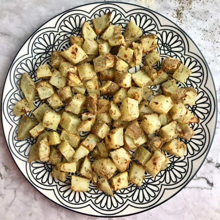 Oil free roasted potatoes on a plate with a black and white pattern.