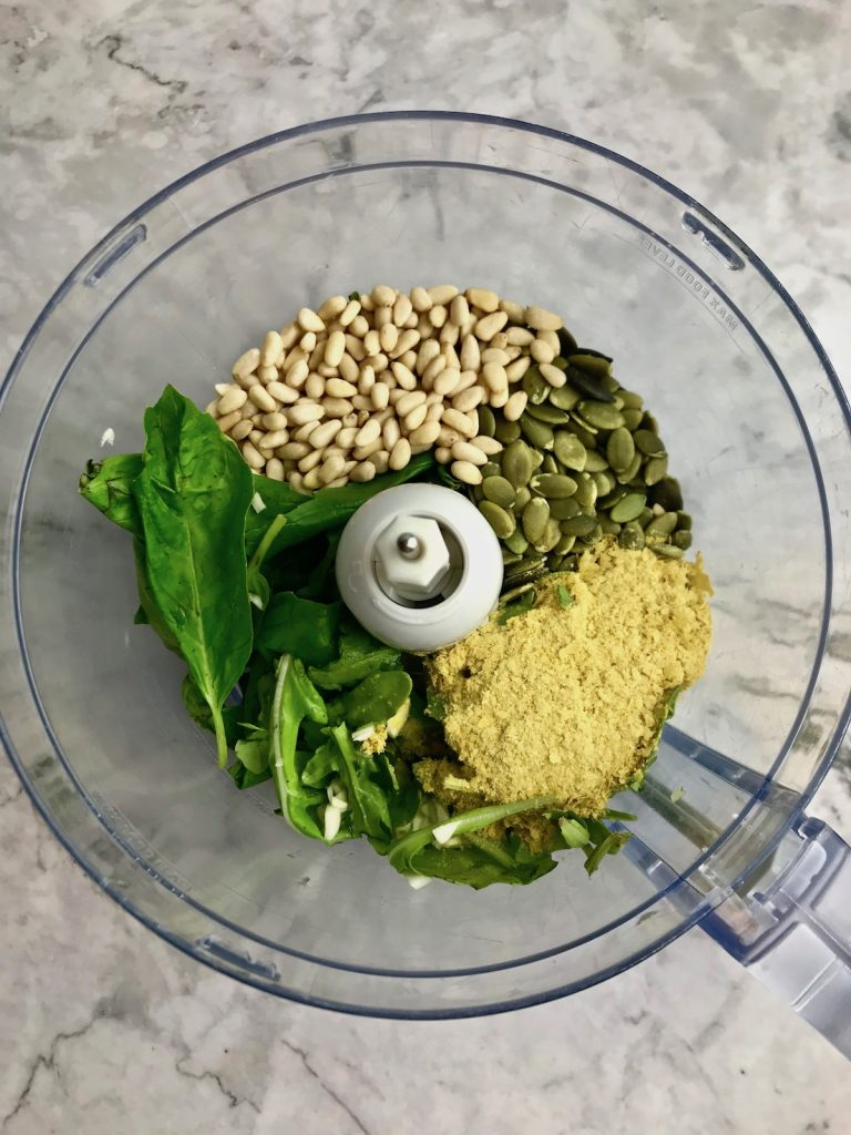 Ingredients for pesto in a food processor, including basil, arugula, pine nuts, pepitas, and nutritional yeast.