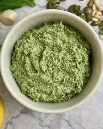 vegan pesto in a small white dish, surrounded by pine nuts, pepitas, garlic, basil, and lemon on the table.
