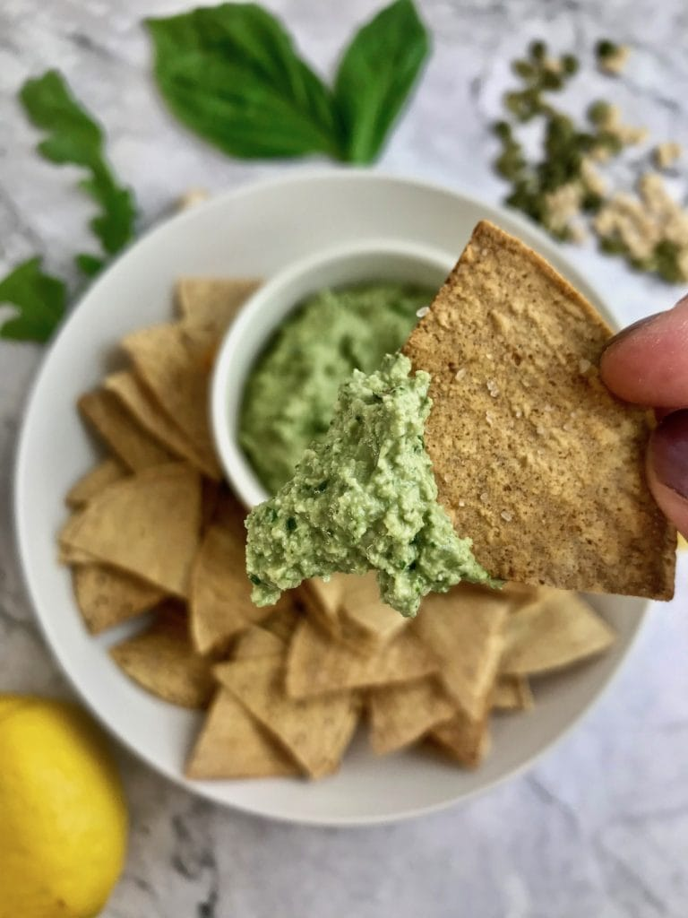 Close up of pesto on a tortilla chip, with ingredients in the background.