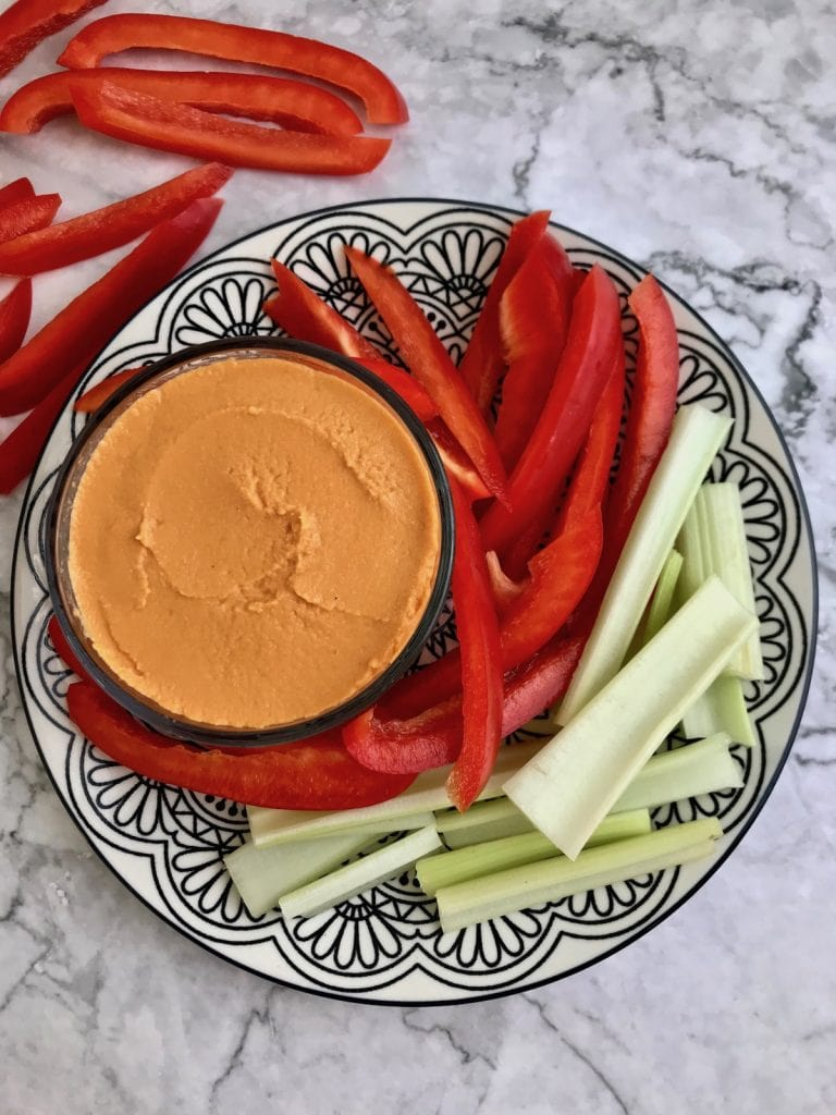 Roasted red pepper hummus surrounded by slices of red pepper and celery.