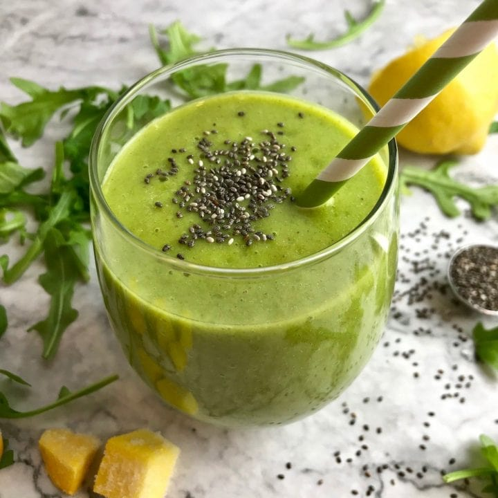 Green smoothie with chia seeds surrounded by arugula, pineapple, and lemon.