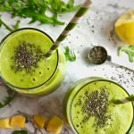 Two green smoothies topped with chia seeds and text that says Arugula Smoothie with Pineapple and Mango.