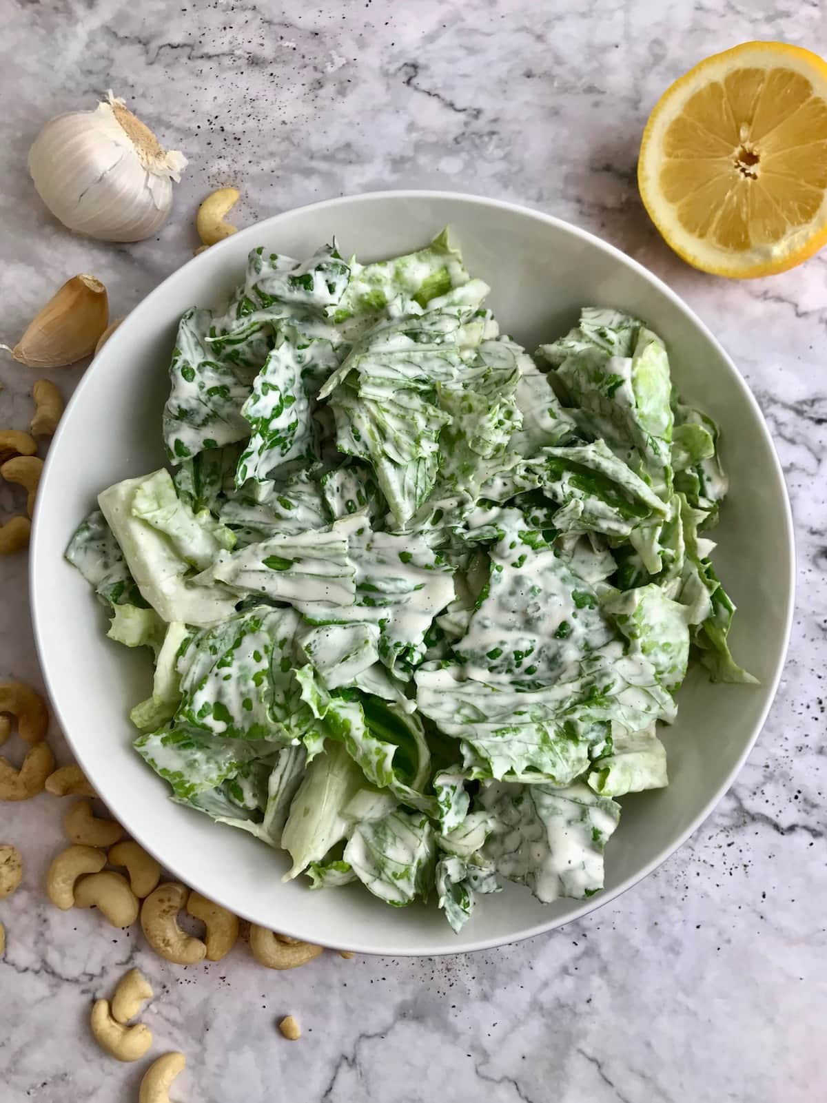 A bowl of romaine lettuce topped with white creamy dressing, and cashews, garlic, and lemon on the table.