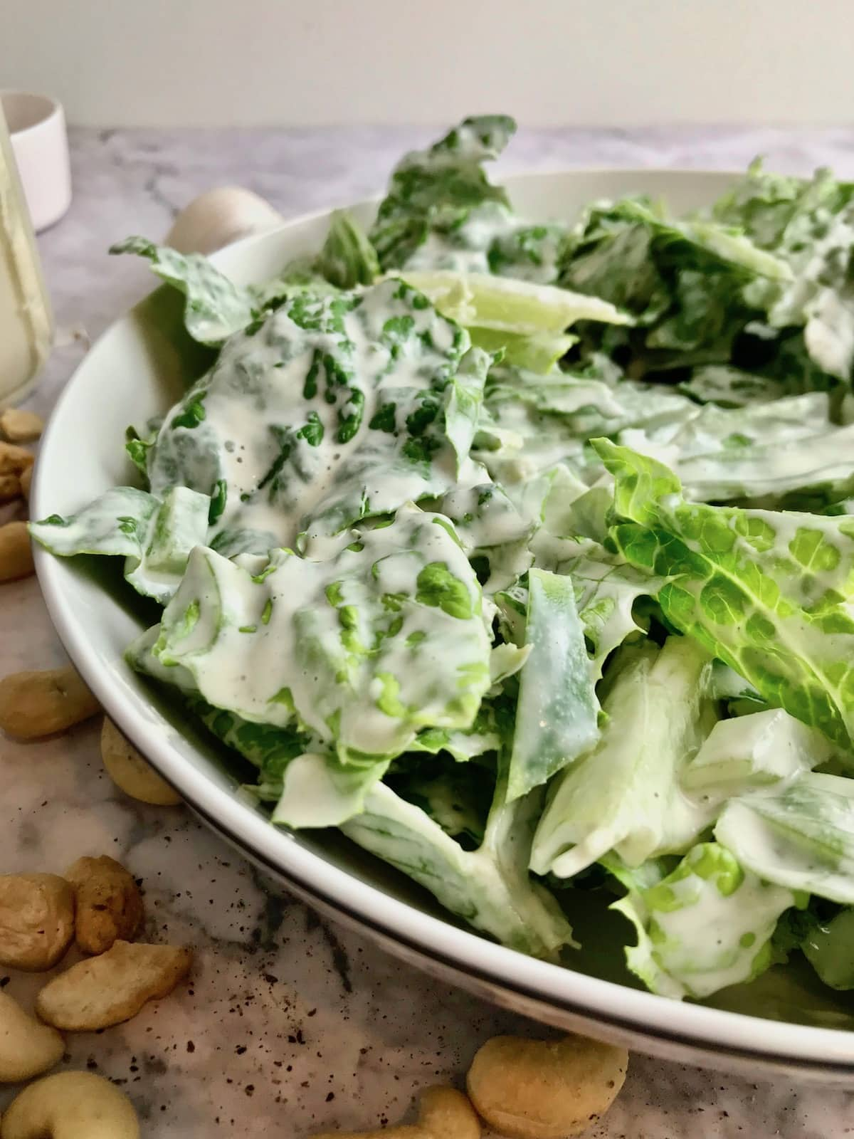 A bowl of romaine lettuce covered in white dressing.
