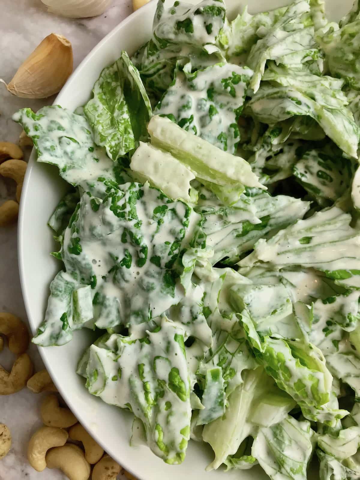 Close up of half a bowl of Romaine lettuce covered in white Caesar dressing.