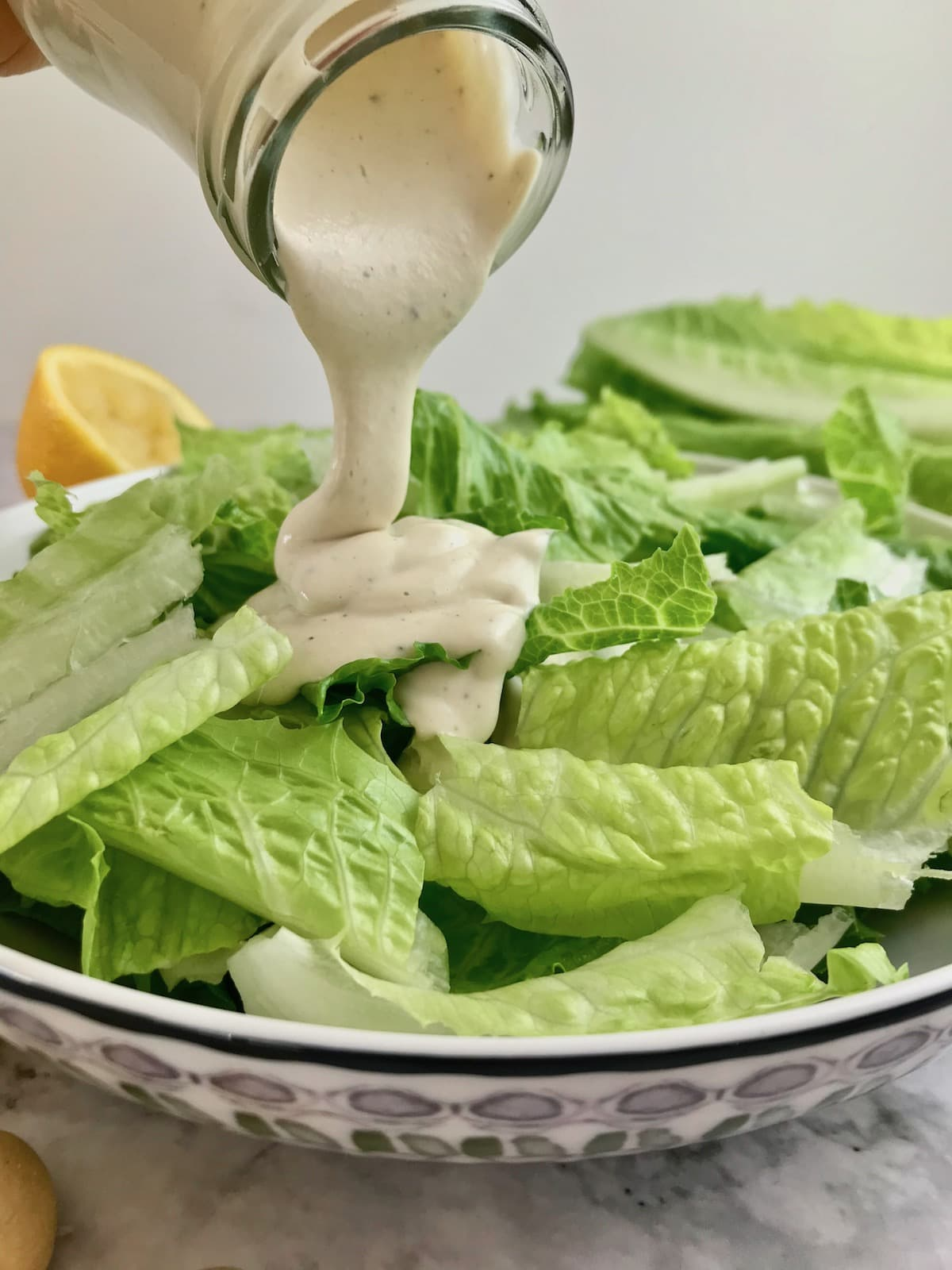 White Caesar dressing being poured onto a bowl or green romaine lettuce.