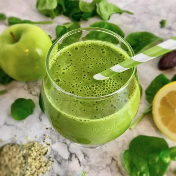 Green smoothie in a stemless wineglass, surrounded by spinach, green apple, lemon, and hemp seeds.