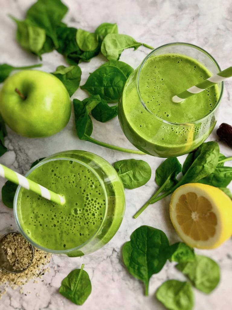Overhead view of two green smoothies, with spinach, green apple, half a lemon, and hemp seeds surrounding them.