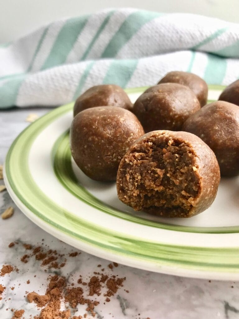Cookie dough balls on a green and white plate with some cocoa powder on the table.