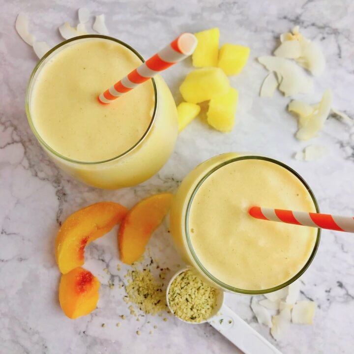 Two yellow smoothies with pineapple and peach slices on the table.