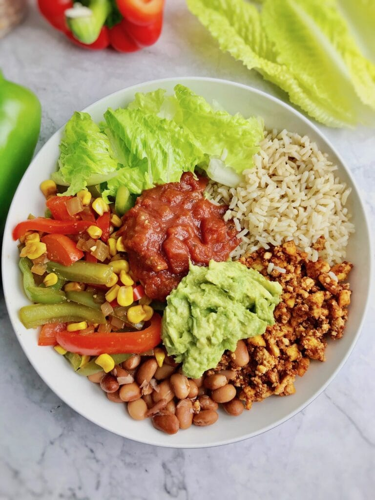 Overhead view of a bowl with rice, vegetables, and salsa and guacamole as toppings.
