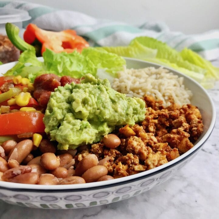 Burrito bowl with tofu, beans, guacamole, and vegetables.