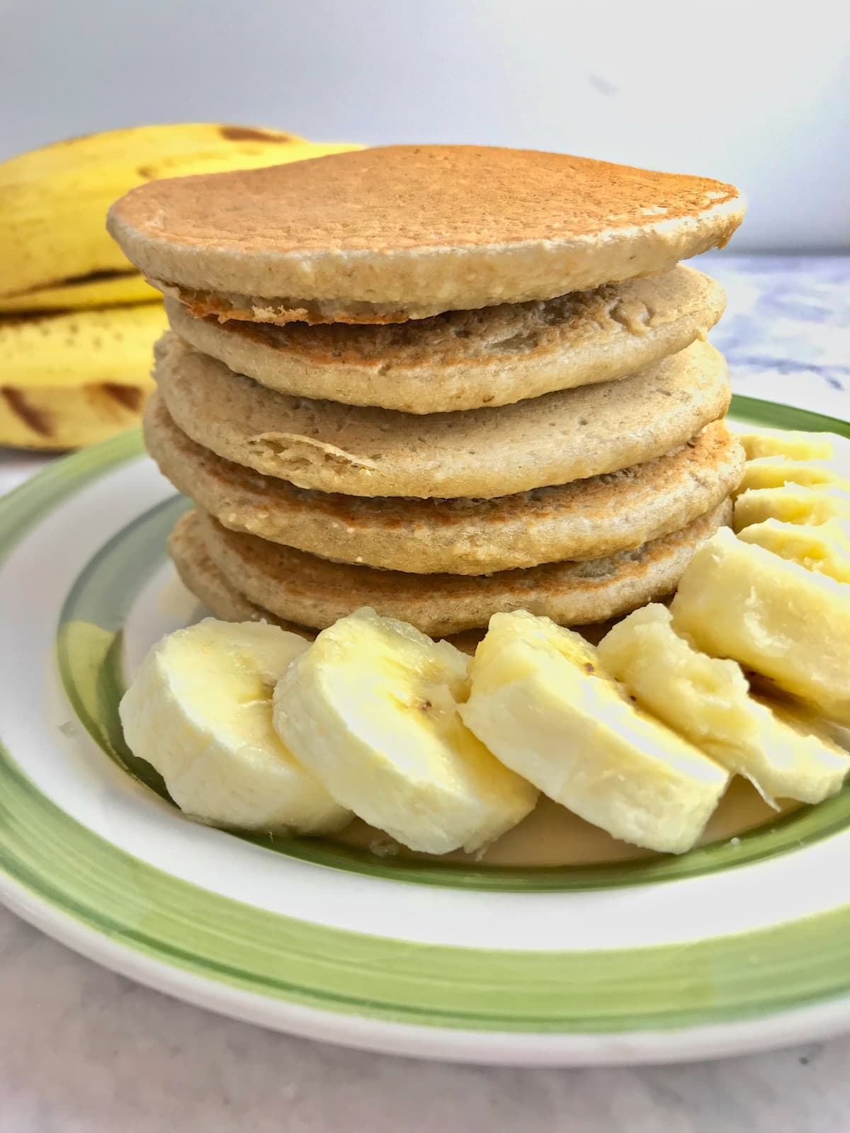 Stack of pancakes with banana slices on a plate.