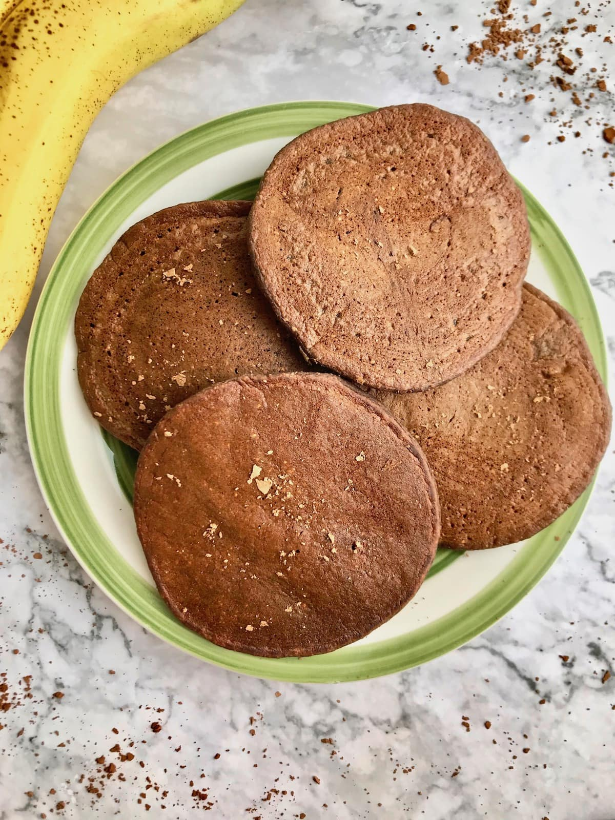 Four chocolate pancakes on a plate, with a banana next to it and cacao powder sprinkled on top.
