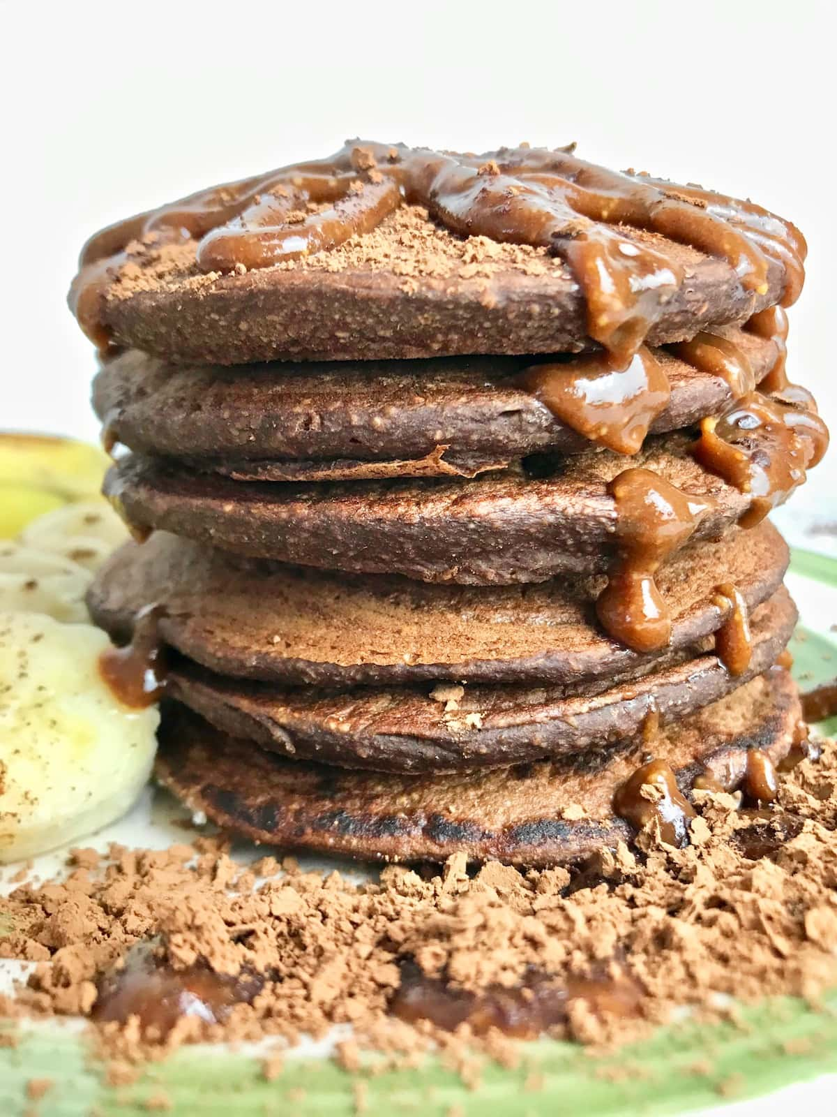 Stack of chocolate pancakes with chocolate syrup and cacao powder on top.