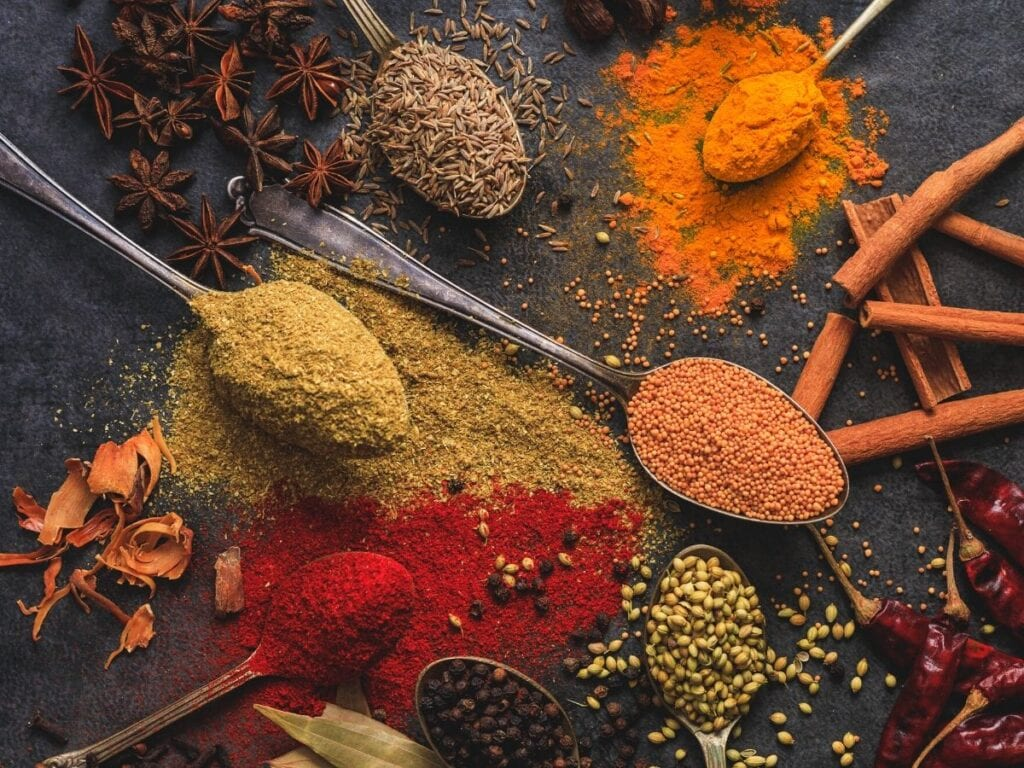 A variety of spices on spoons. Includes red, yellow, and orange powdered spices.
