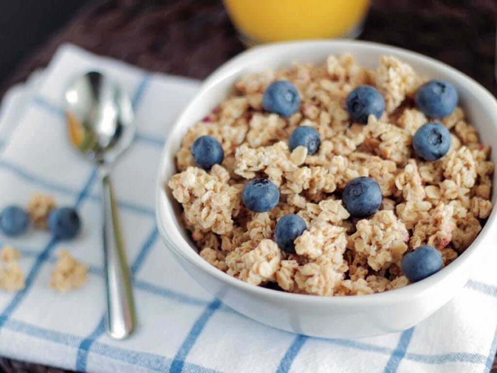 A bowl of oatmeal topped with blueberries.