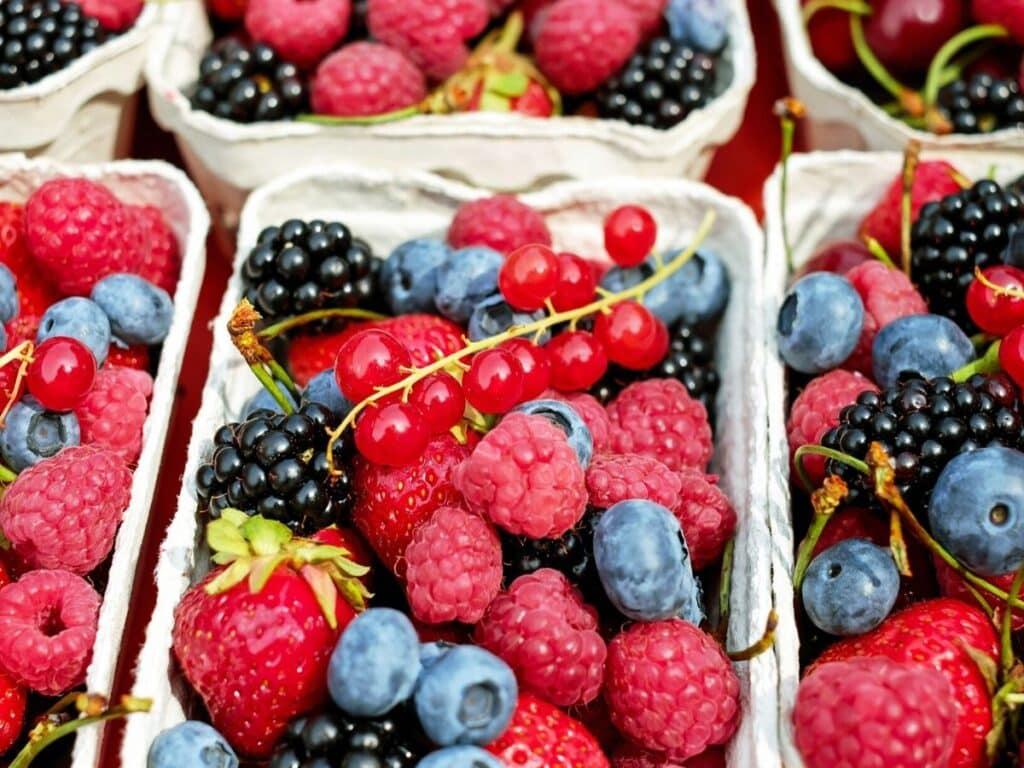 Containers of berries, including raspberries, blueberries, strawberries, and blackberries.