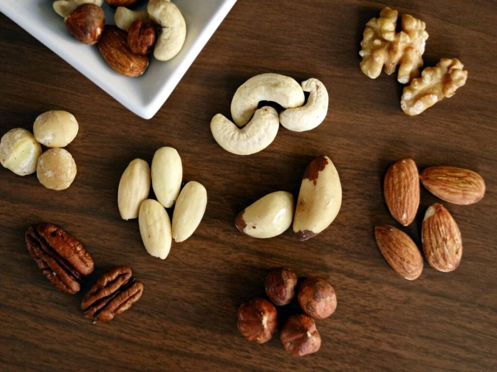 Nuts laid out on a table, including almonds, walnuts, cashews, hazelnuts, and pecans.
