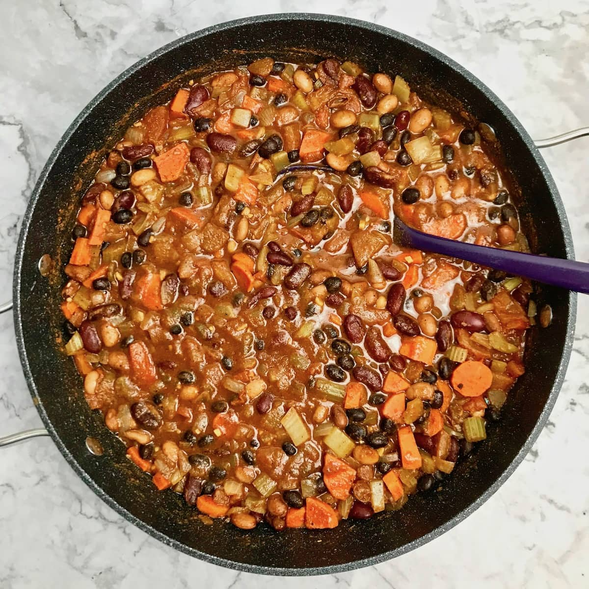 Vegan bean chili in a dutch oven pot with a purple serving spoon in it.