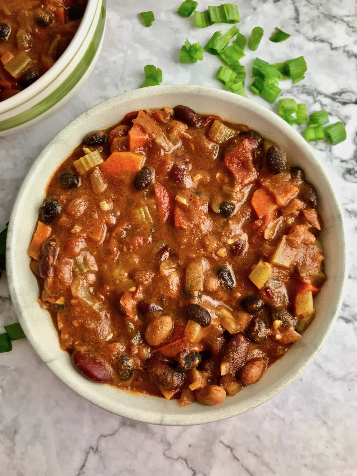 A bowl of veggie and bean chili on a table with chopped green onion.