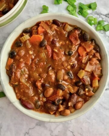 A bowl of vegan bean chili on a table with chopped green onion.