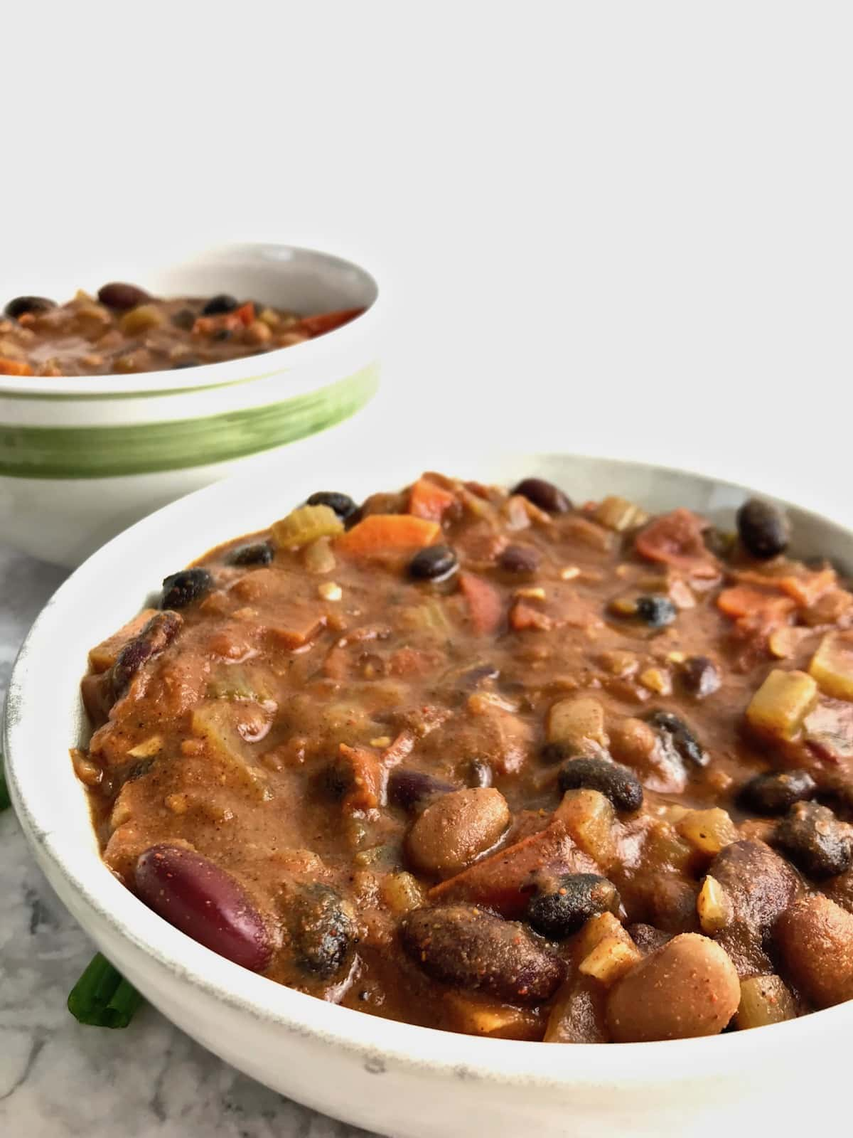 Close up of 3 bean chili in a bowl with another bowl of chili in the background.