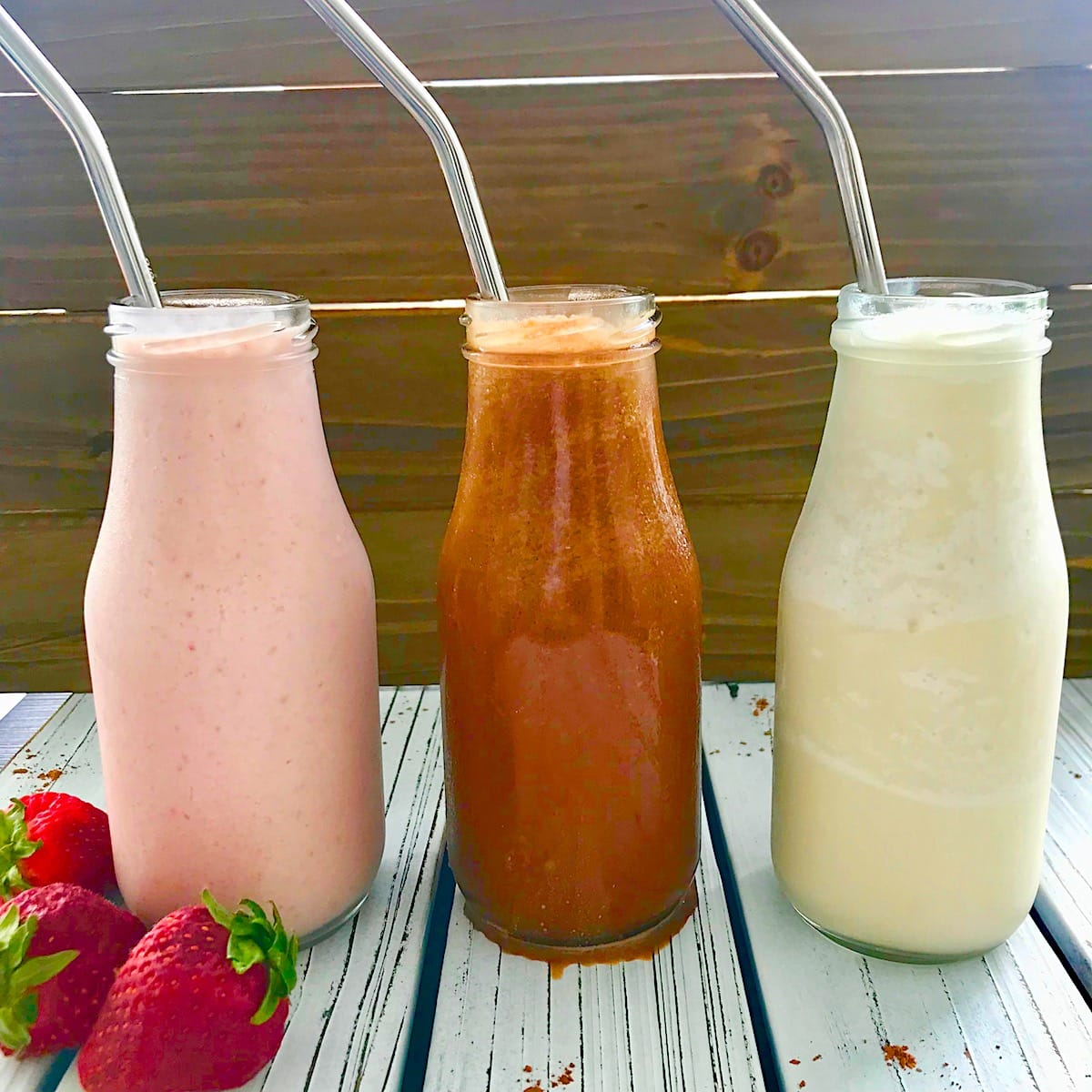 Three milkshakes in a row, starting with strawberry on the left, followed by chocolate and vanilla.